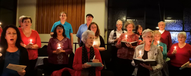 The choir holds candles while singing at a Christmas Eve service.