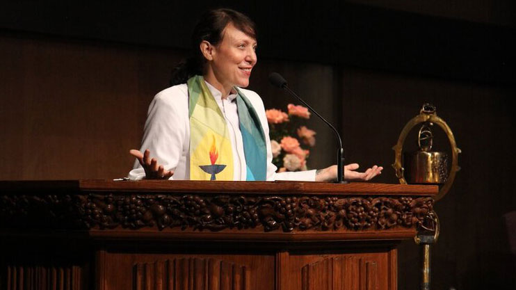 Rev. Lissa Gundlach at the pulpit, facing right.
